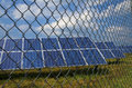 Solar panels behind rusty fence Royalty Free Stock Photo