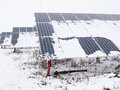 Solar panels covered with snow rows of in small power plant Stock Photography