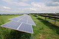 Solar panels in the green field and sky with white clouds Royalty Free Stock Photo