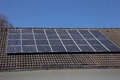 Solar panels on a house roof an array of photovoltaic mounted to supply renewable domestic electricity by converting the radiant Royalty Free Stock Photos
