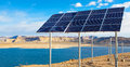 Solar panels on lake powell along the shore of with water and mountains in the background Stock Image