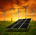 Solar panels and wind turbine in the setting sun Royalty Free Stock Images