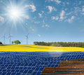 Solar power cells rapeseed field and windmills on the horizon Stock Photography