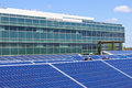 Solar powered office ground level panel array in front of building Stock Photo