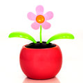 Solar powered plastic flower which moves when the sun shines on a white background Stock Images