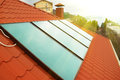Solar water heating system geliosystem on the red house roof Royalty Free Stock Image