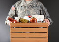 Soldier holding food drive box closeup of a in fatigues a wooden full of canned and packaged for a holiday charity horizontal Royalty Free Stock Photo