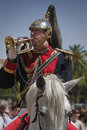 Soldier playing the trumpet inspired by dragons body of isabel ii and presented a helmet ponytail and coat of arms of brotherhood Stock Photos