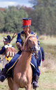 A soldier rides a brown horse an unknown in blue uniform decorated by yellow epaulettes borodino historical reenactment battle Royalty Free Stock Photography