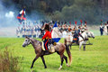 A soldier rides a brown horse an unknown in blue uniform decorated by yellow epaulettes borodino historical reenactment battle Royalty Free Stock Photos