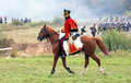 A soldier rides a brown horse an unknown in red uniform borodino historical reenactment battle between russian and french armies Stock Image