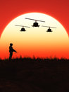 Soldier in the sunset this image shows a with flying helicopter Royalty Free Stock Image