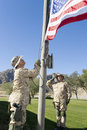 Soldiers raising united states flag against the sky Stock Photos