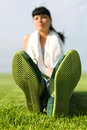Sole of shoes green on grass tired sportswoman Royalty Free Stock Images