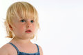 Solemn little blonde girl portrait of a with blue eyes looking off to one side solemnly on a plain white background Stock Photography