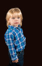 Solemn little boy against a dark background in blue and white checked shirt Royalty Free Stock Photography