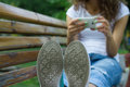 Soles shoe closeup girl in jeans using a mobile phone the background sitting on bench rest the park Royalty Free Stock Photos
