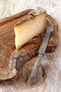 Solid cheese on olive tray and vintage knife on wooden surface Stock Images