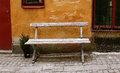 Solitary bench old worn chained to old house Royalty Free Stock Images