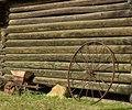 Solitary wagon wheel leaning against log cabin Royalty Free Stock Image