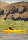 Solitude man fishing in a kayak on a river in the summer Royalty Free Stock Image