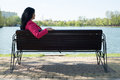 Solitude woman on bench in park sad sitting looking to the water Stock Photos