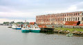 Solovki island beach moored offshore fishing seiners and ruined brick building Stock Photography