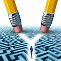 Solution crossroad business concept as a three dimensional maze or labyrinth being erased by two pencils clearing a cross road Stock Image
