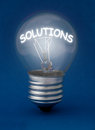 Solutions lit bulb highlighting the word Royalty Free Stock Photo