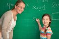Solving equation portrait of smart teacher and schoolgirl standing by blackboard and looking at camera Stock Image