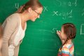 Solving equation portrait of smart teacher and schoolgirl standing by blackboard and looking at one another Royalty Free Stock Photos