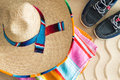 Sombrero beach towel and sneakers on sand wide brimmed straw lying a colorful striped with a pair of tropical with a Royalty Free Stock Photo