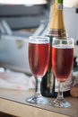 Some champagne two glasses of bubbly pink on a counter with the bottle in the background Stock Photography