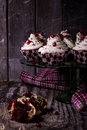 Some chocolate cakes on a wooden background dish with cake covered with butter cream and pomegranate seeds Stock Photo
