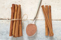 Some cinnamon sticks tied with a natural rope on a white wooden table next a spoon with powdered top view Stock Photo