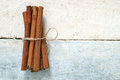 Some cinnamon sticks tied with a natural rope on a white wooden table top view empty space for editor s text Stock Image
