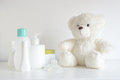 Some cosmetic, perfume and lotion bottles on a white table next to a teddy bear and a pacifier. Royalty Free Stock Photo
