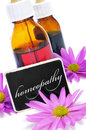 Some dropper bottles and a blackboard with the word homeopathy written on it and pink flowers Stock Photos