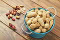 Some peanuts in a turquoise bucket on wooden table Royalty Free Stock Image