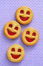 Some smiley biscuits on a purple woven background Stock Photos