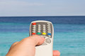 Somebody hand pointing remote control towards sea summer s day Stock Images