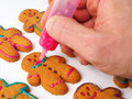 Someone decorating gingerbread cookies white background Royalty Free Stock Images