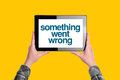 Something went wrong message on digital tablet computer display woman holding device isolated yellow background Royalty Free Stock Photo