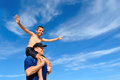 Son balancing on dad s shoulders father holding his at the beach Stock Photo