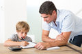 Son doing homework while father standing by at table in house Stock Photo