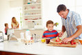 Son helping father to prepare family breakfast in kitchen with wife and daughter sitting background Stock Photography