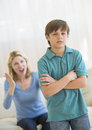 Son ignoring angry mother at home standing arms crossed while Stock Photo