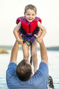 Son lifted up by father out of lake little boy the water his dad Stock Images