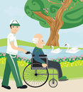 Son pushing senior father on wheelchair outdoors for a walk Stock Photography