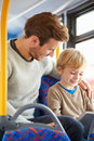 Son using digital tablet on bus journey with father looking over shoulder smiling Stock Images